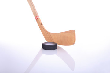 Hockey stick and puck on reflective surface
