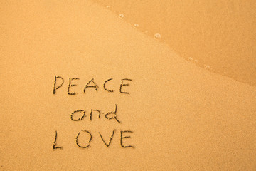 Peace and Love - text written by hand in sand on a beach