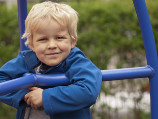 four year old boy at the playground smiling into camera