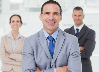 Employee posing with his colleagues on background