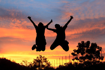 young couple jumping  before sunset