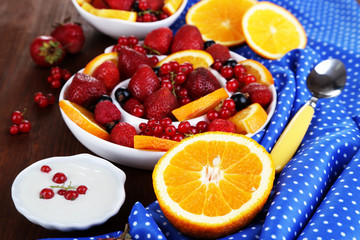 Useful fruit salad in plates on wooden table close-up