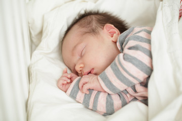 Small sleeping baby in bed (up to 20 days)