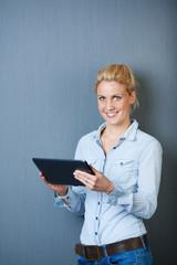 lächelnde blonde frau mit tablet-computer