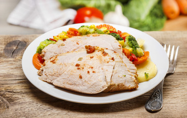 Baked meat with vegetables on wooden table. Fresh raw vegetables