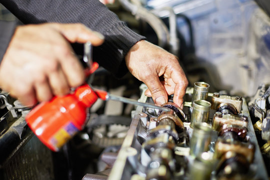 Hands of mechanic, who lubricates car engine