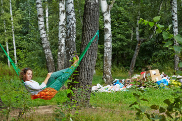 Young barefooted woman with discontented face lies in hammock