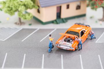 Miniature mechanics working on a car with hood up