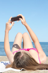 woman photographing herself with mobile phone on the beach