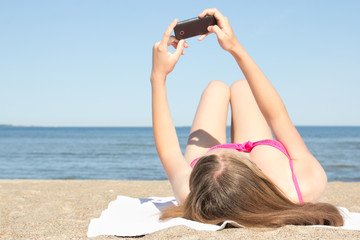 young woman photographing herself with mobile phone on the beach