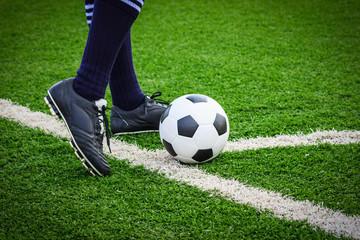 foot kicking soccer ball on corner