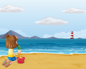 A young girl playing with the sand in the beach