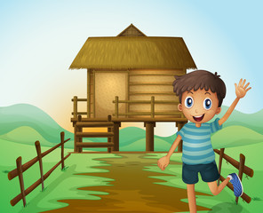 A boy waving his hand in front of a nipa hut