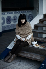 Young woman in knitted clothing drink hot tea