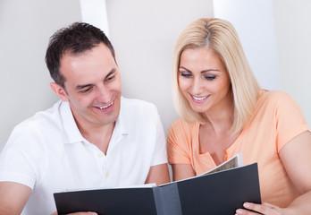Happy couple looking at photo album