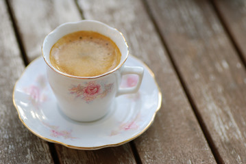 espresso in a cup with flower pattern and gold linen