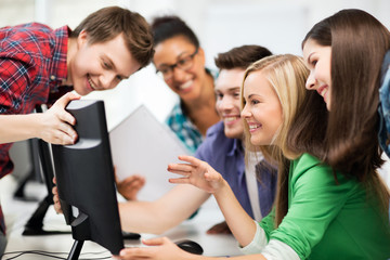 students looking at computer monitor at school