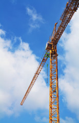 Yellow tower crane on a beautiful blue sky background