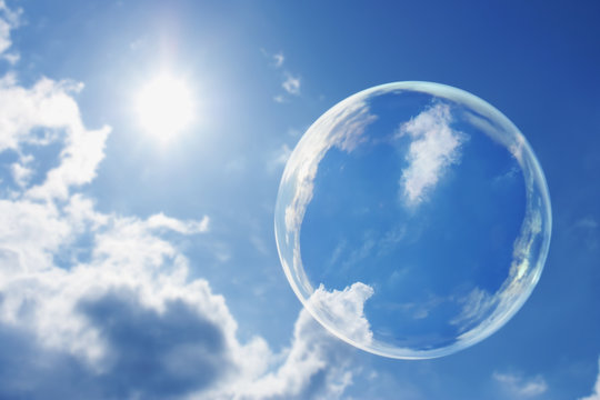Floating Soap Bubble Against Clear Sunlit Blue Sky and Clouds