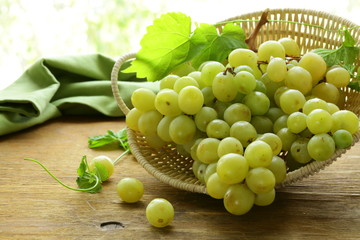 Organic white grapes in a basket on a wooden table Fototapete