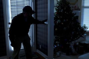 Burglar Breaking In To Home At Christmas Through Back Door