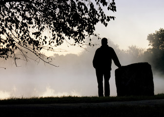 Silhouetted Adult Male Stands Alone Thoughtfully By Foggy Lake
