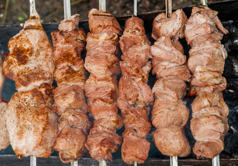 slices of meat prepare on fire with smoke