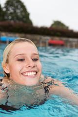 Junge Frau beim Brustschwimmen im Freibad