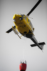Fire rescue heavy helicopter with water bucket, goes to a fire.