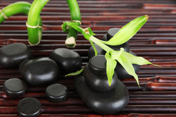 Spa stones and bamboo on bamboo mat background