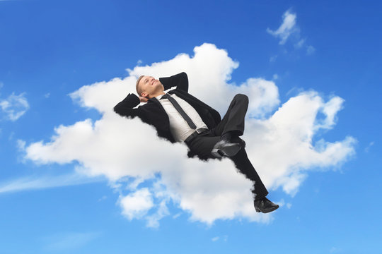 Businessman sleeping in a cloud