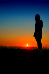 girl silhouette at sunset with blue sky