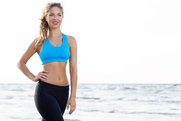 Fitness girl workouts on the beach
