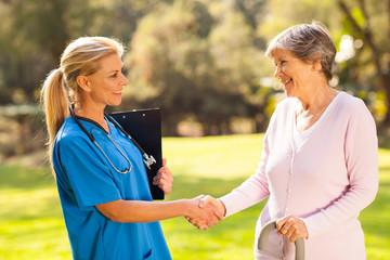 mid aged nurse handshaking senior patient