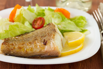 fried fish with salad and lemon on the plate