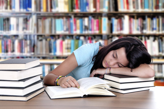 Tired student sleeping at the desk in a library