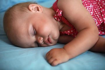 Little baby girl sleeps in the bed