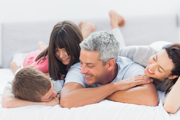 Cute family lying on bed and talking together