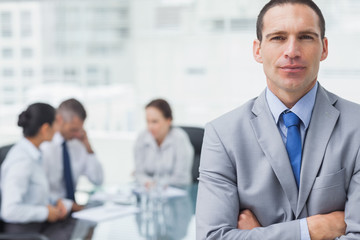 Serious businessman posing with coworkers on background