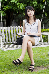 Beautiful Asian woman on white wooden swing.