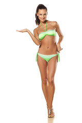 young brunette in a bikini holding  imaginary object