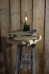 kerosene lamp and stack of old books
