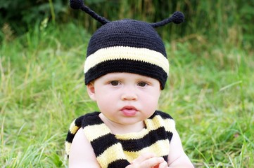 thoughtful baby in bee costume outdoors