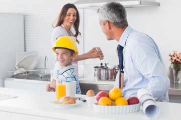 Boy trying on fathers hard hat with parents laughing