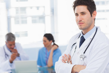 Serious doctor looking at camera with colleagues behind