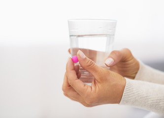 Closeup on pill and glass of water in hand of young woman