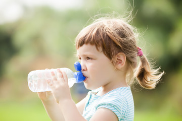 child drinking from plastic bottle