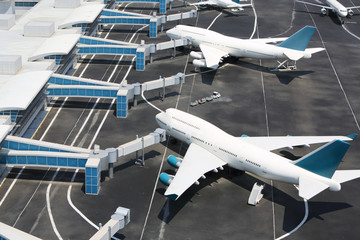 Models of modern white aircraft standing at miniature airport.