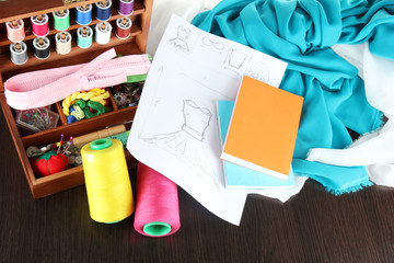 Sewing kit in wooden box,cloth and sketch on wooden table