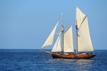 old historical tall ship (yacht) with white sails in blue sea